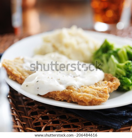 chicken fried steak with southern style peppered milk gravy - stock photo