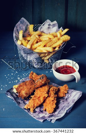Chicken fries strips and legs on paper with basket of  French fries and bowl of ketchup sauce over blue wooden table. Turquoise wooden wall at bachground. Rustic style. With retro filter effect - stock photo