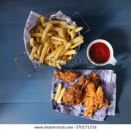 Chicken fries strips and legs on paper with basket of  French fries and bowl of ketchup sauce over blue wooden table. Top view. Square image - stock photo
