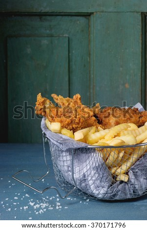 Chicken fries strips and legs with French fries in metal basket over blue wooden table with sea salt. Turquoise wooden wall at bachground. Rustic style - stock photo