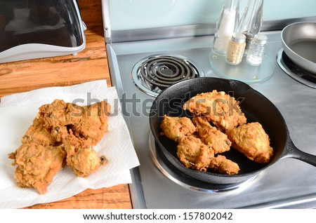 Chicken frying in old cast iron skillet on  modern electric range with some on paper towels ready to serve. - stock photo