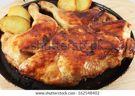 Chicken grilled, roasted, in a frying pan with potato