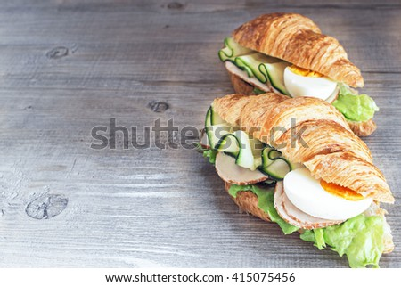 Chicken ham and  egg breakfast sandwich on a croissant on a rustic wooden table. Selective focus. - stock photo