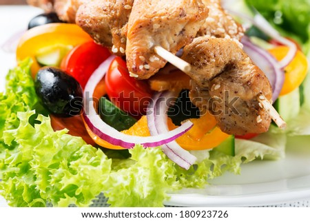 Chicken kebab over salad - stock photo