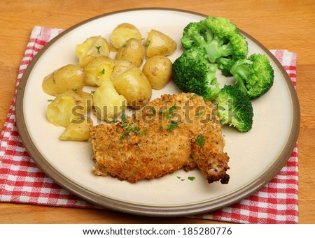 Chicken Kiev with broccoli and new potatoes.