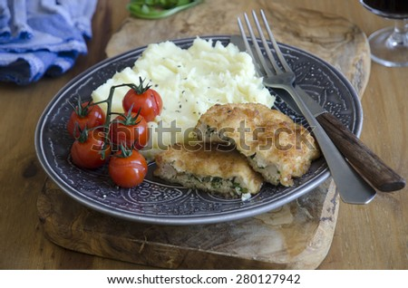 Chicken kievs with mashed potatoes and roasted cherry tomatoes - stock photo