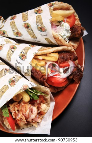 chicken lamb and pork rolled on a pita bread  on a black background - stock photo