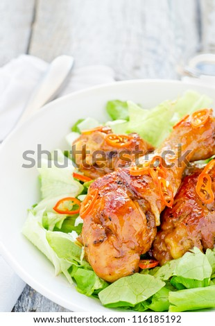 Chicken legs cooked in black beer with salad and slices of red peppers - stock photo