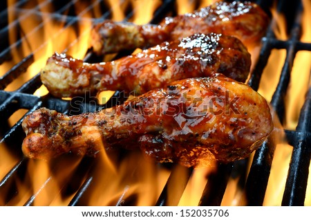 Chicken legs grilling over flames on a barbecue  - stock photo