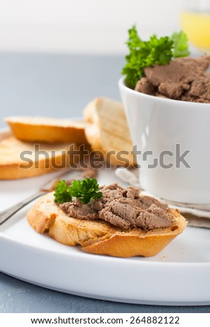 Chicken liver pate on bread and in bawl,  selective focus - stock photo