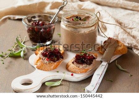 Chicken liver pate with onion jam on bread and in jar - stock photo