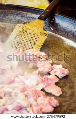 Chicken meat roasting on a large paella pan, outdoors food market - stock photo