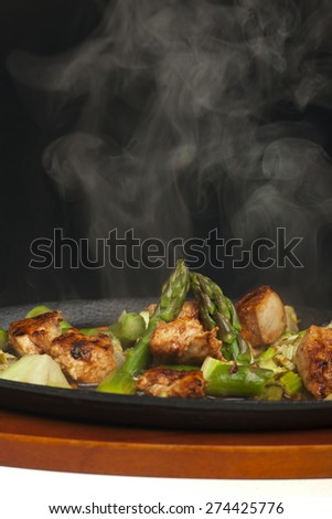 chicken meat with asparagus in a sizzler  - stock photo