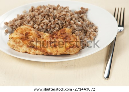 Chicken meat with buckwheat kasha on a white plate, closeup shot