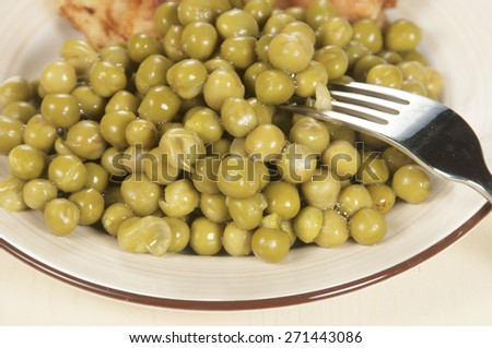 Chicken meat with green peas on a ceramic plate, closeup