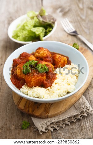 Chicken meatballs with tikka sauce and couscous - stock photo