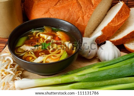 chicken noodle soup a popular and favorite variety worldwide surrounded by ingredients and crusty bread - stock photo