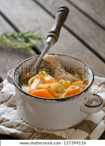 Chicken noodle soup in ceramic pot, selective focus - stock photo