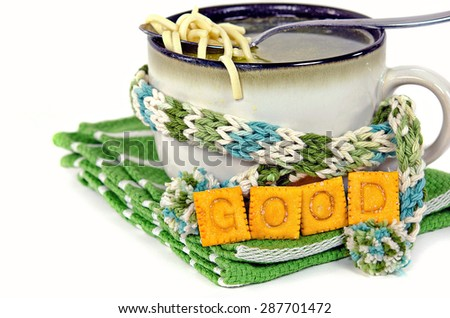 chicken noodle soup in soup mug with winter scarf and crackers on striped towel - stock photo