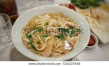 Chicken noodle with hot soup in a white bowl.Asia food