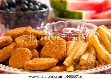 Chicken nuggets and french fries with watermelon and blueberries in the background.