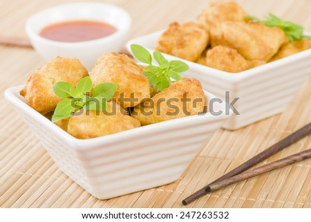 Chicken Nuggets - Battered and deep fried chicken pieces served with chilli sauce. - stock photo