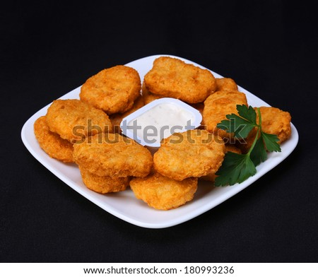 Chicken nuggets on plate with mayo over black background - stock photo