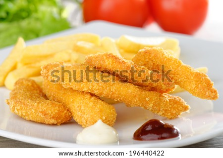 chicken nuggets/sticky fingers and french fries on a white plate  - stock photo