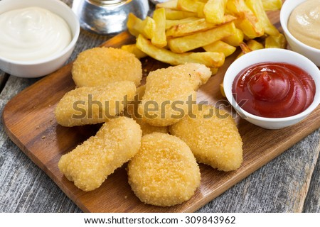 chicken nuggets with french fries and different sauces on wooden board, top view