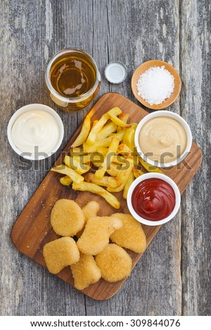 chicken nuggets with french fries, different sauces and a glass of beer, top view, vertical - stock photo