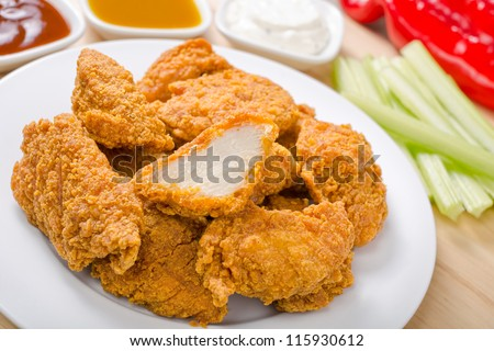 Chicken nuggets with three dipping sauces. - stock photo