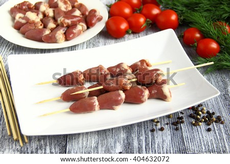 Chicken offal. Closeup of fresh raw chicken hearts with  tomato and dill. - stock photo