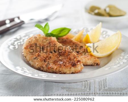 Chicken or pork schnitzel with lemon wedges, selective focus - stock photo