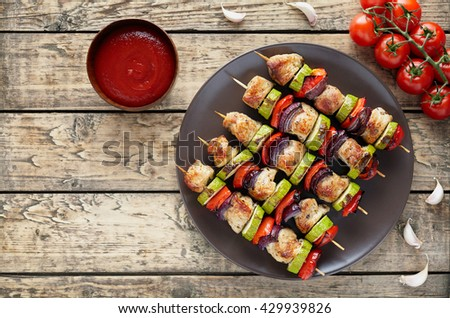 Chicken or turkey meat shish kebab skewers with ketchup, tomatoes and garlic on rustic wooden table background. Traditional barbecue grill food - stock photo