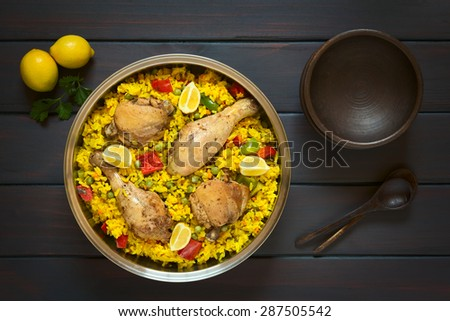 Chicken paella, a traditional Valencian (Spanish) rice dish made of rice, chicken, peas and capsicum and served with lemon in  pot, photographed overhead on dark wood with natural light - stock photo