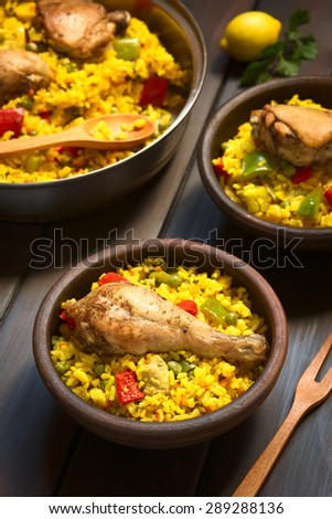 Chicken paella, a traditional Valencian (Spanish) rice dish made of rice, chicken, peas and capsicum , photographed on dark wood with natural light (Selective Focus, Focus on the chicken thigh) - stock photo