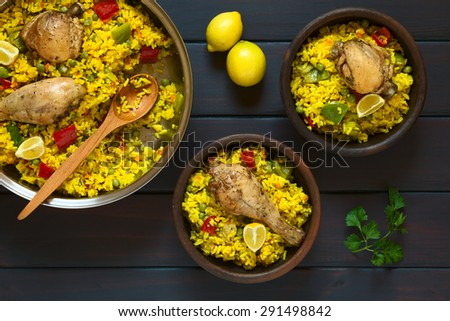 Chicken paella, a traditional Valencian (Spanish) rice dish made of rice, chicken, peas and capsicum, served with lemon in a pot and rustic bowls, photographed on dark wood with natural light - stock photo