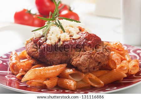 Chicken parmesan, breaded chicken steak with tomato sauce and macaroni pasta