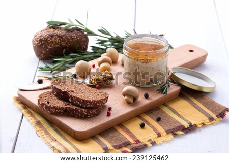 Chicken pate in jar and sliced bread with french mustard, champignon and rosemary - stock photo