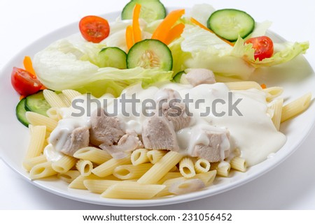 Chicken pieces on penne pasta topped with white bechamel sauce and served with a salad - stock photo