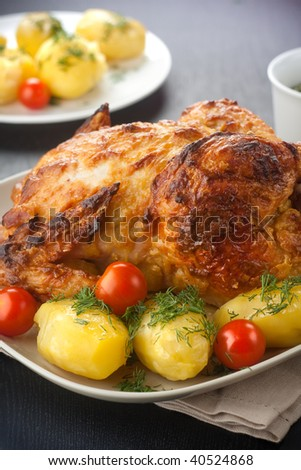 Chicken roasted in mustard sauce garnished with boiled potatoes and cherry tomatoes