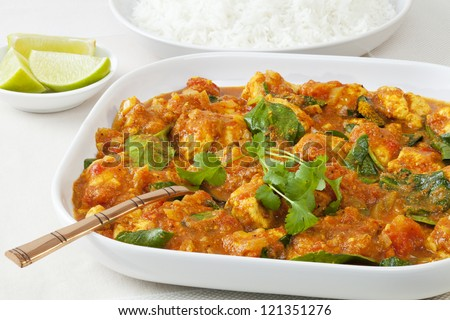 Chicken sag or saag, a spicy chicken dish with baby spinach, served with basmati rice and lime. - stock photo