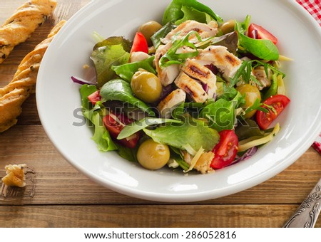 Chicken salad on a rustic wooden table. - stock photo