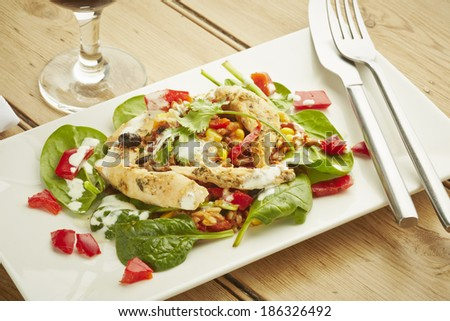 Chicken salad on white dish and wooden table top - stock photo