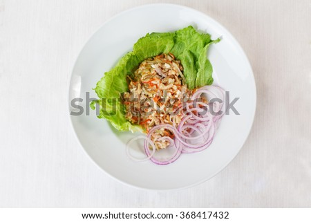 chicken salad, pickled cucumber and carrot on lettuce red onion round saucer top menu Series ase - stock photo