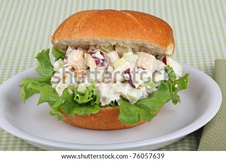 Chicken salad sandwich with apple pieces on top of lettuce