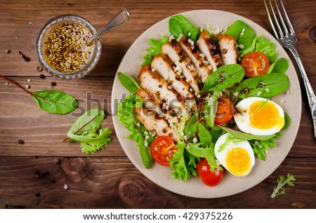 Chicken salad with leaf vegetables, chard, eggs, bulgur and cherry tomatoes - stock photo