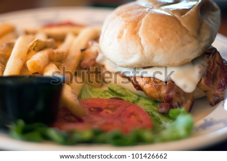 Chicken Sandwich on a fresh Kaiser roll with cheese and bacon and a side of french fries. - stock photo
