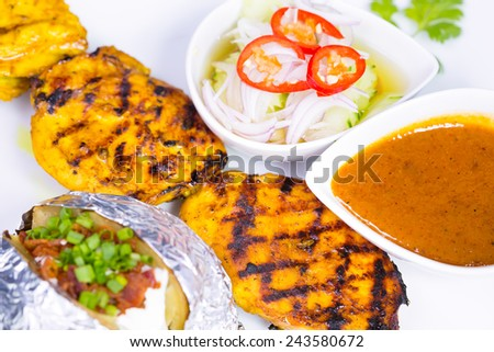 Chicken satay with delicious peanut sauce on white plate - stock photo