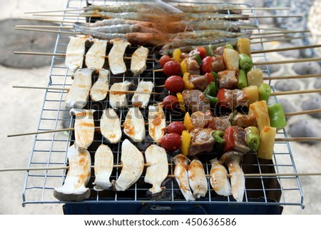 chicken shish kebab on bbq grill in sauce on skewers with tomatoes and peppers. shrimp and eringii mushroom grill. - stock photo